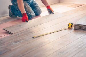 man fitting a solid wood floor in a property